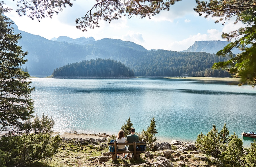National Parks In Montenegro - A young couple sitting on a bench. Black lake. Durmitor
