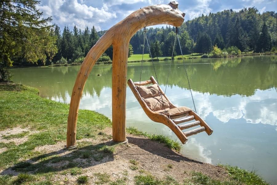 Lakes In Slovenia - Wooden swing over Lake Bloke in Nova Vas, Slovenia on a sunny day