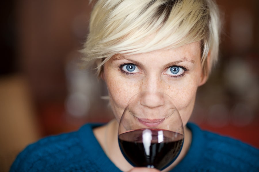Blond Woman Drinking Red Wine In Restaurant