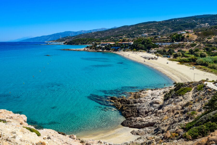Paradise Greek Aegean Sea beach in Livadi at the Ikaria island in a quiet summer day with flat clear blue water. Near Armenistis